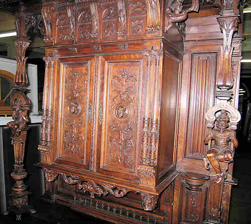 This is a picture of a superb walnut carved cabinet accented with Jesters. This is the top of the cabinet