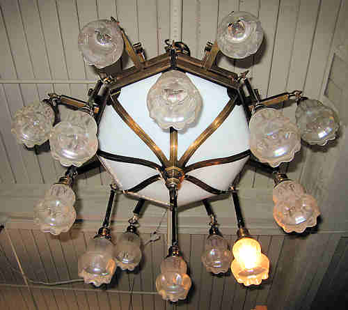 exqusite arts and crafts bronze lamp with 16 acid etched shades and a bent panel milk glass shade in the center.
